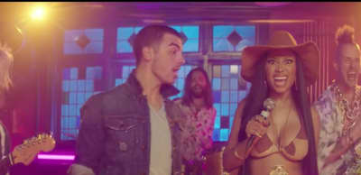 "Nicki Minaj Parties With Joe Jonas In DNCE's ""Kissing Strangers"" Video"