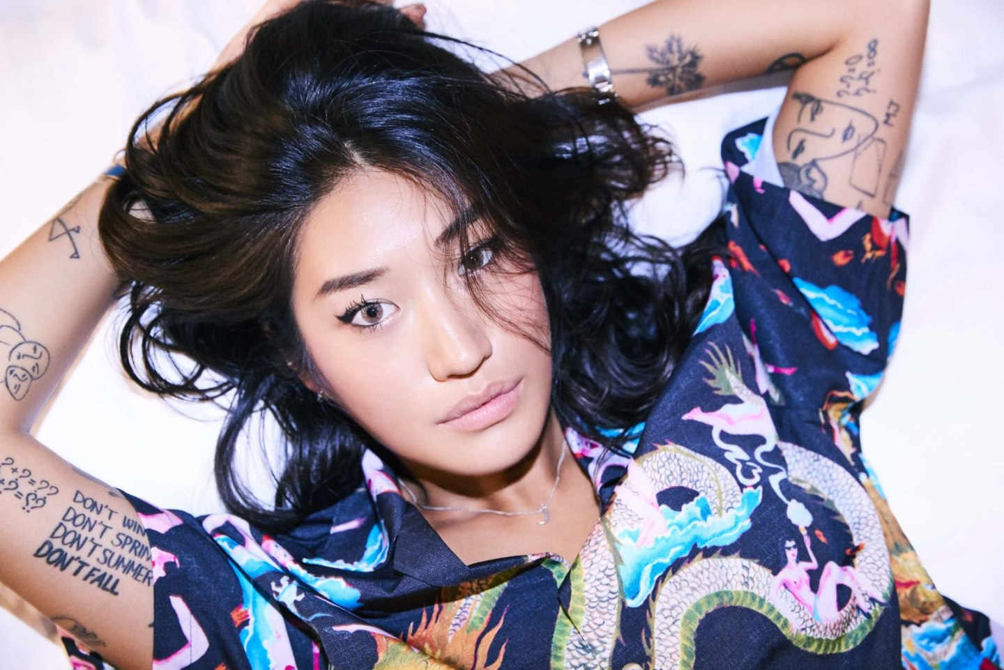 Musician Peggy Gou laying down with hands behind her head.